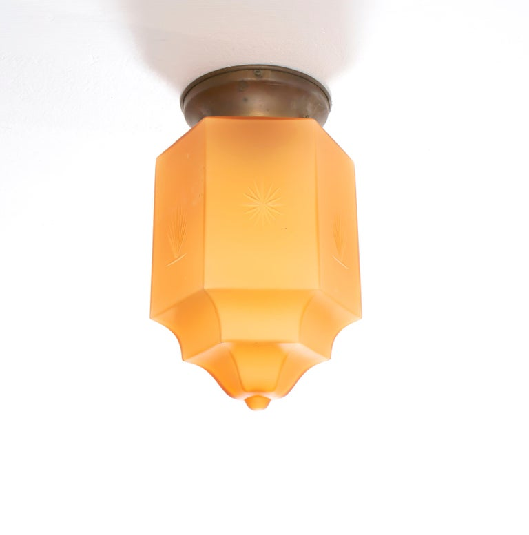 Decorative and very and rare ceiling light in Havana glass, with decorated surface and metal base. Designed and made in Norway from ca 1930s first half. The lamp is fully working and in good vintage condition. It is fitted with one E27 bulb holder