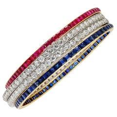 Art Deco Four Piece Diamond Ruby Sapphire Gold Bangle Bracelet Set