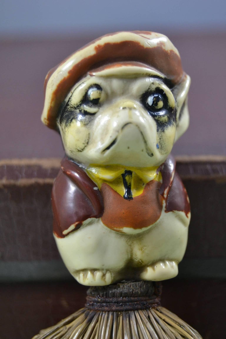 Antique hand brush with a Bulldog dog on top. Art Nouveau, Art Deco figural hand brush This figural mini broom, table broom wears a cartoon, comical bulldog character. He wears a hat, a jacket and pants and is made of solid celluloid and