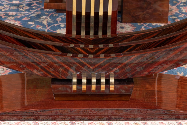 Console is made out of Macassar wood. Table top is elevated by 3 curved wooden elements. They are stabilized with trapezoid base. On the back of the console there is wooden panel with 5 brass decorative lines.  Condition is excellent.   France,