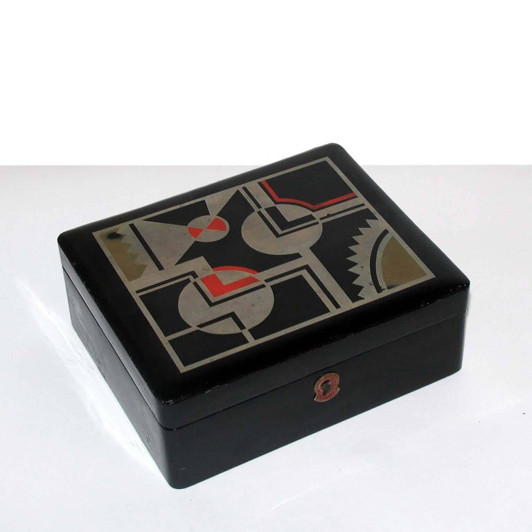 Art Deco French lacquered box, jewelry box, geometric decor, in the style for Jean Dunand. Decorative or jewelry Art Deco box, France, circa 1930. Black lacquered, lid decorated with geometric design in silver leaf, light red and beige lacquer.