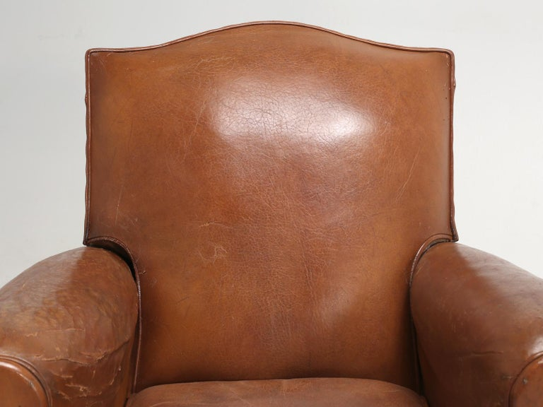 French Art Deco leather club chairs, sill in their original leather. Restored frames and padding, while the leather went through a conservation process. We would classify, this particular pair of French leather club chairs, on the medium to smaller