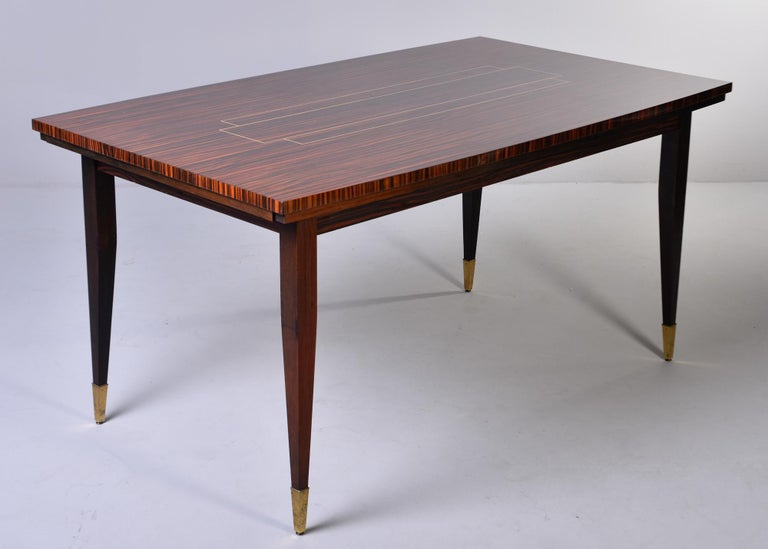 French Art Deco era dining table features a highly figured Macassar top with contrasting center design, dark wood base with tapered legs and brass feet, circa 1940s. Unknown maker.   Very good vintage condition with some surface scuffs and minor