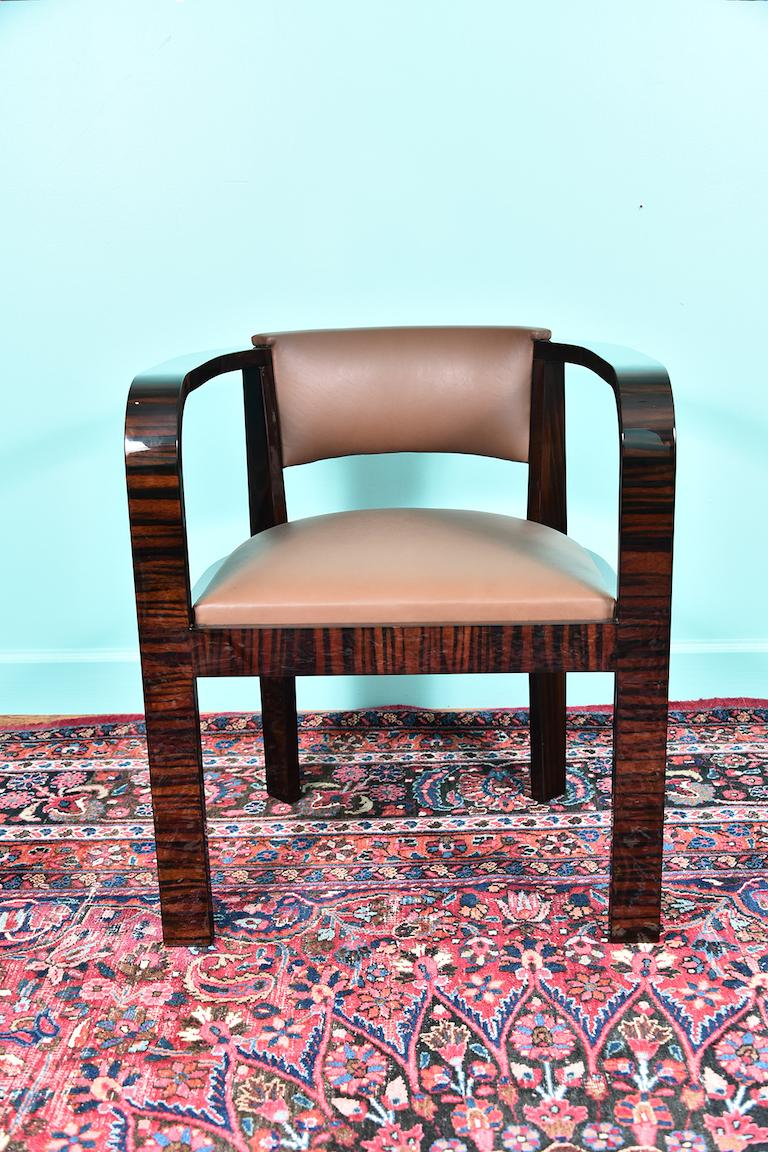 Chair is re-upholstered with similar color leather. There is opening between rectangular back and seat. Chair has full length armrests that are curved and are becoming 2 front supporting legs.