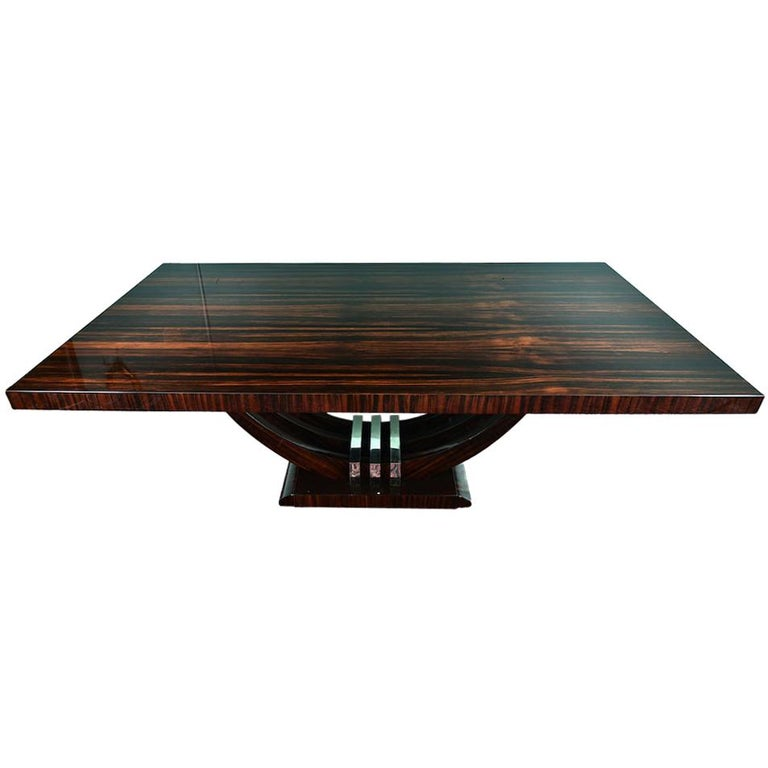 Art Deco French dining table in Macassar Table is made out of Macassar wood and the beautiful wood grain is clearly shown on the tabletop. 3 semi-circular legs are connected with each other in the middle by 3 chrome brackets. Trapezoid shape base is