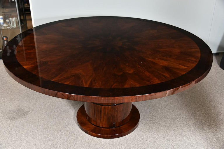 """Dining room table is done with a high quality walnut wood. Table top has ebonized ribbon of wood on the edge. Base is a circular form and a wide leg is elevating tabletop.   Condition is perfect. Restored  France, circa 1930s.   Measures: 65"""""""