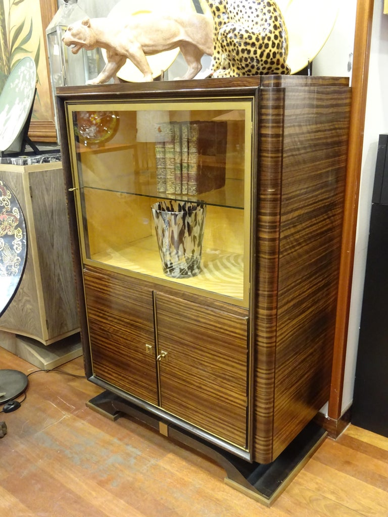 One of a kind refined bookcase by E.J Ruhlman workshop French Art Deco, in an refined hardwood and lemon wood in the interior, brass to frame and embellish. It has one door on the top of the cabinet and one shelf in the interior, glass and brass