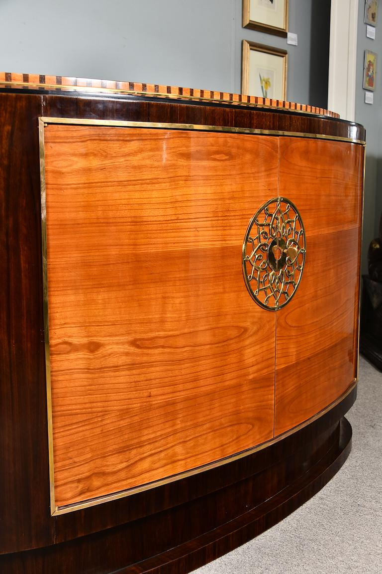 Sideboard is made out of fine walnut wood. It has 2 keyed front doors. Inside there are 2 drawers on top and single shelf in the middle.  Different polish creates striking juxtaposition of wood color. Middle front part is embellished