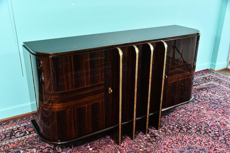 Art Deco French sideboard with 4 brass vertical lines  Sideboard is made out of Macassar wood. It has 2 keyed spacious drawers on the sides. Inside there are shelves and smaller drawers. Between side drawers there are 4 decorative brass vertical