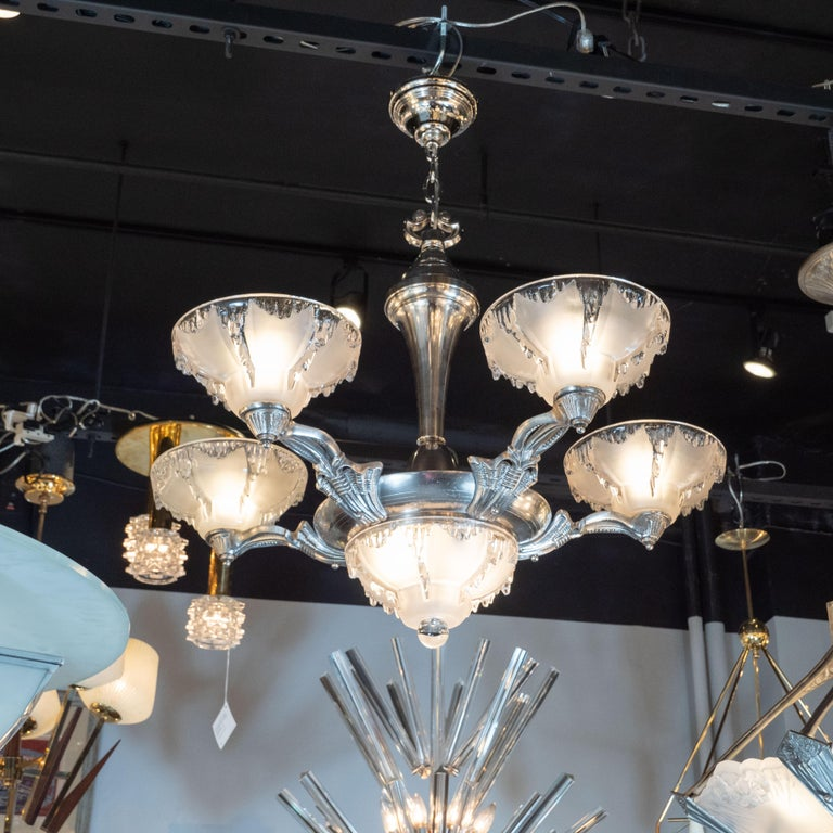 This glamorous and dramatic Art Deco five-arm chandelier was realized by the esteemed maker Ezan & Petitot in France, circa 1930. It features curved sculptural arms with abstract and geometric detailing that connect to a circular body all in