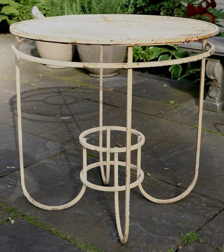 Very stylish center table made by Woodard Furniture Company. Unusual and nit often seen form, originally designed as a center table, but also suitable for use as a cafe or side table as well. Currently in later French Vanilla paint finish, which