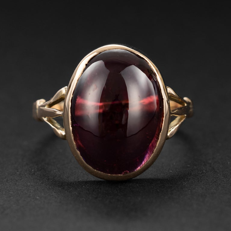 A glowing wine-red natural oval garnet cabochon is the luminous focal point of this antique 1920s ring. Crafted by hand in 9k rose gold, the cabochon measures 15.54mm x 11.58 and weighs approximately 5 carats. The ring is open in the back, so when