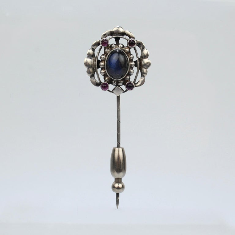 A rare Georg Jensen silver stick pin.  Model no. 17.   Set with a central Labradorite cabochon and four small amethyst cabochons. (And accompanied by an added safety slide for extra security).  Dates between 1917 and 1927.  A rare early Jensen piece