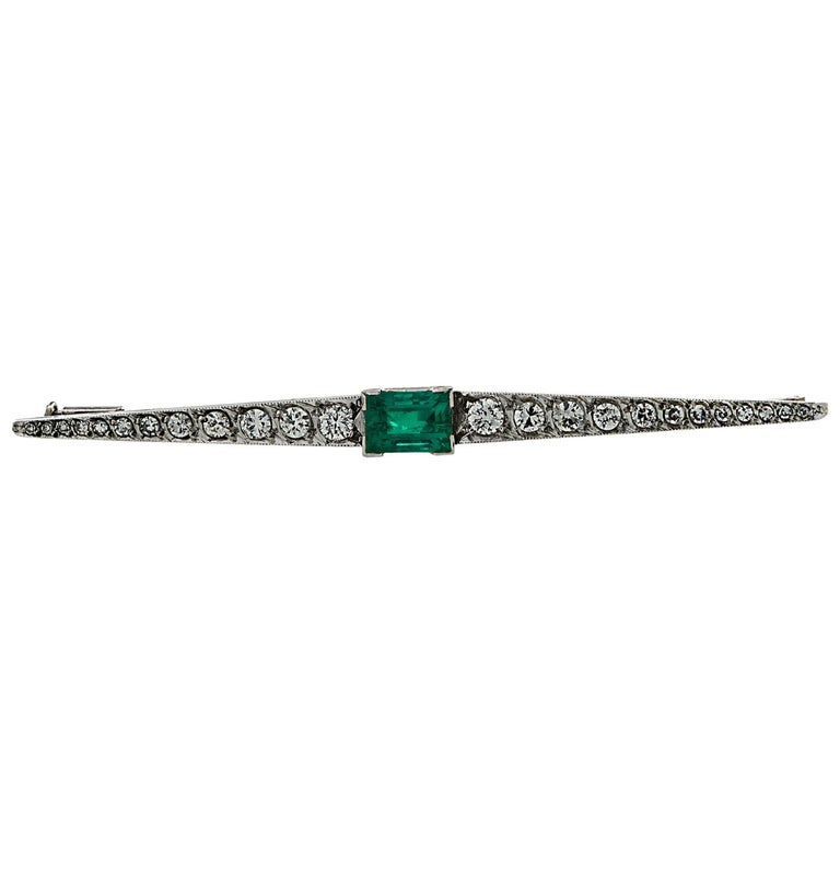 Fabulous Art Deco Brooch Pin crafted in Platinum, showcasing a GIA certified emerald cut Colombian Emerald weighing approximately 1.25 carats total, adorned with 24 Old European and single cut Diamonds weighing approximately .50 carats total, G