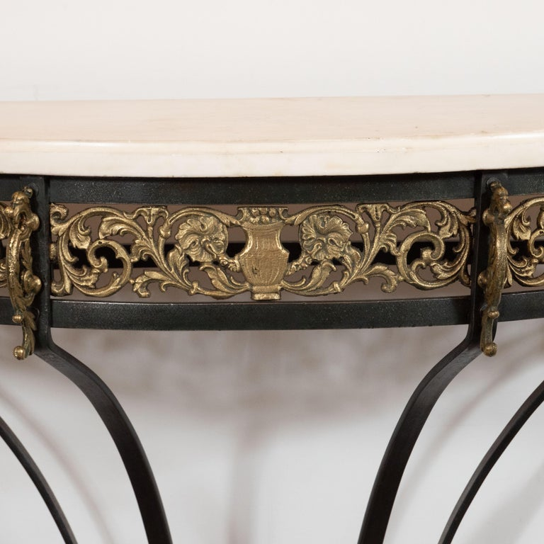 This sophisticated Art Deco console table was realized in the United States, circa 1935. Realized in the manner of Edgar Brandt, it features a demilune form Carrara marble top with a subtle grisaille palette and variegated grain. It is supported by