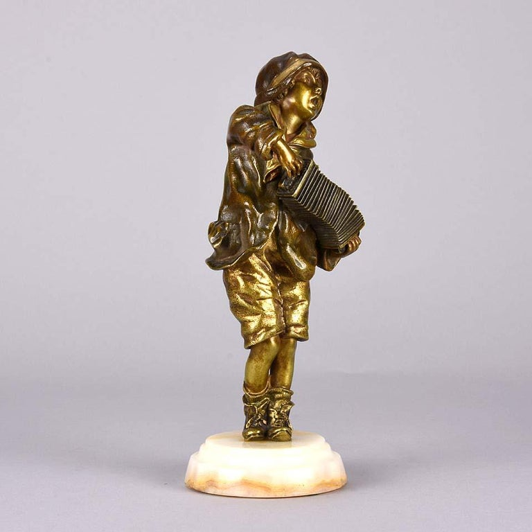A delightful early 20th century gilt and enameled Art Deco bronze figure of a young lad playing the accordion, with wonderful detail and color, raised on a variegated onyx plinth, signed Chiparus on back of bronze.