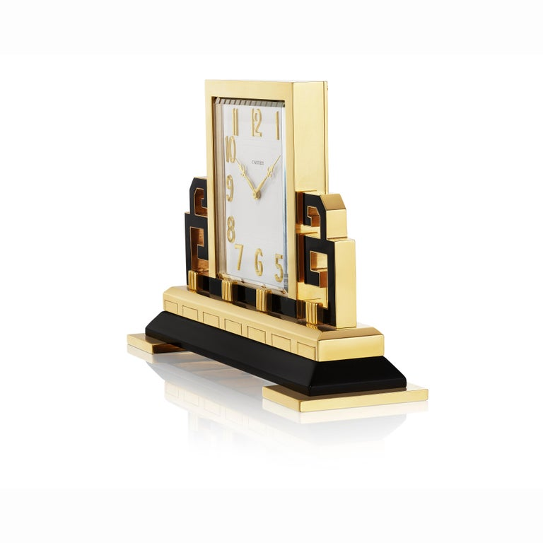 A clock composed of a square dial in gilt brass set on a trellis base composed of black enamel in the form of a Chinese screen; striped nickel watch movement, fifteen jewels, unadjusted with cut and compensated bimetallic balance on an overcoiled