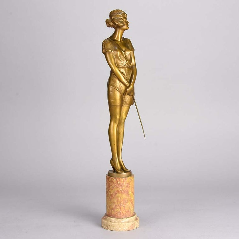 A fabulous Art Deco gilt bronze figure of a beautiful woman wearing a loose fitted figure hugging dress and high heels holding a riding whip, with excellent color and very fine hand finished detail, signed Zach.