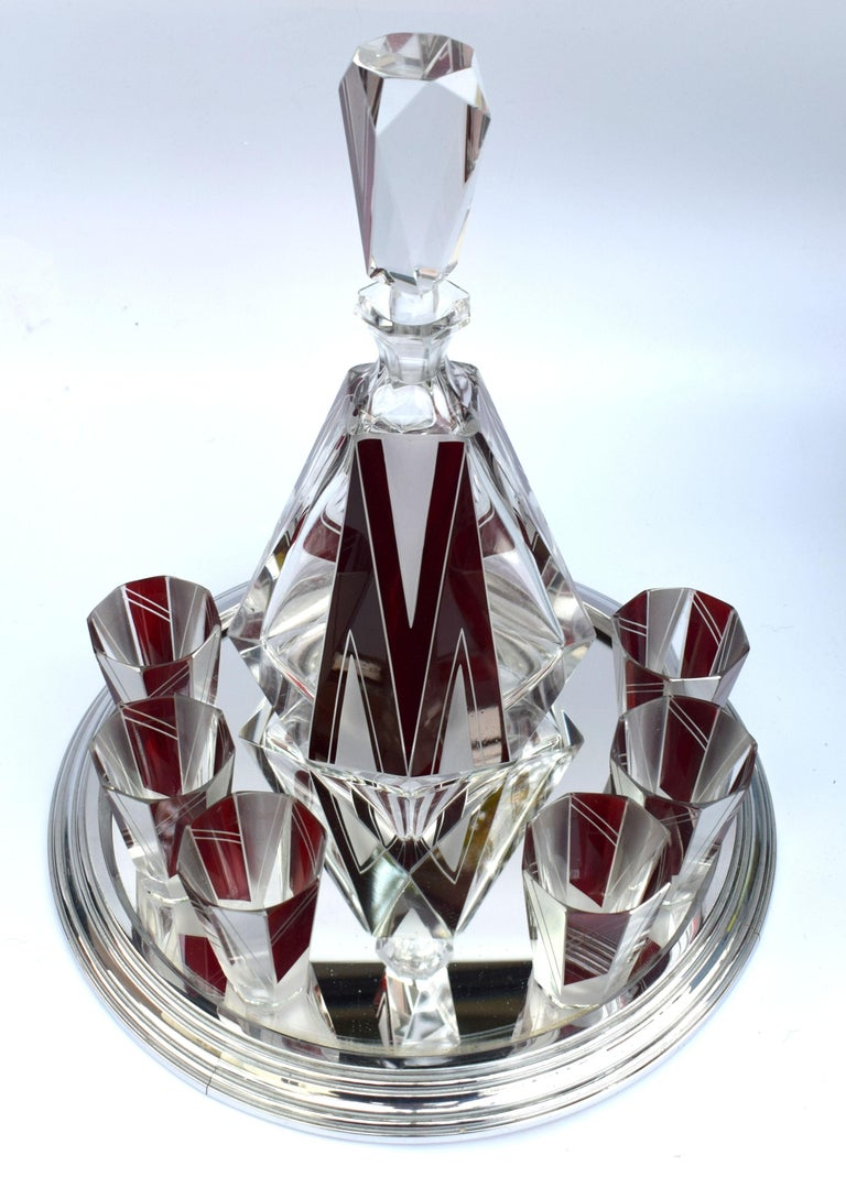 Wonderfully stylish glass decanter dating to the 1930s with a strong vibrant enameling in ruby red and silver overlay, this set really does stand out from the rest. Stunning shape and cut, small shot glasses. Comprises decanter and stopper with 6
