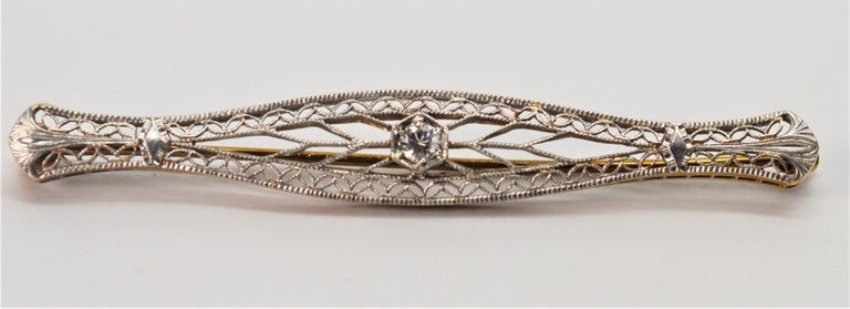 Elegant Art Deco fourteen carat gold filigree pin brooch with center .05 carat miner's cut diamond. Crafted in classic bowed-shape and measures 2-1/4 inches.