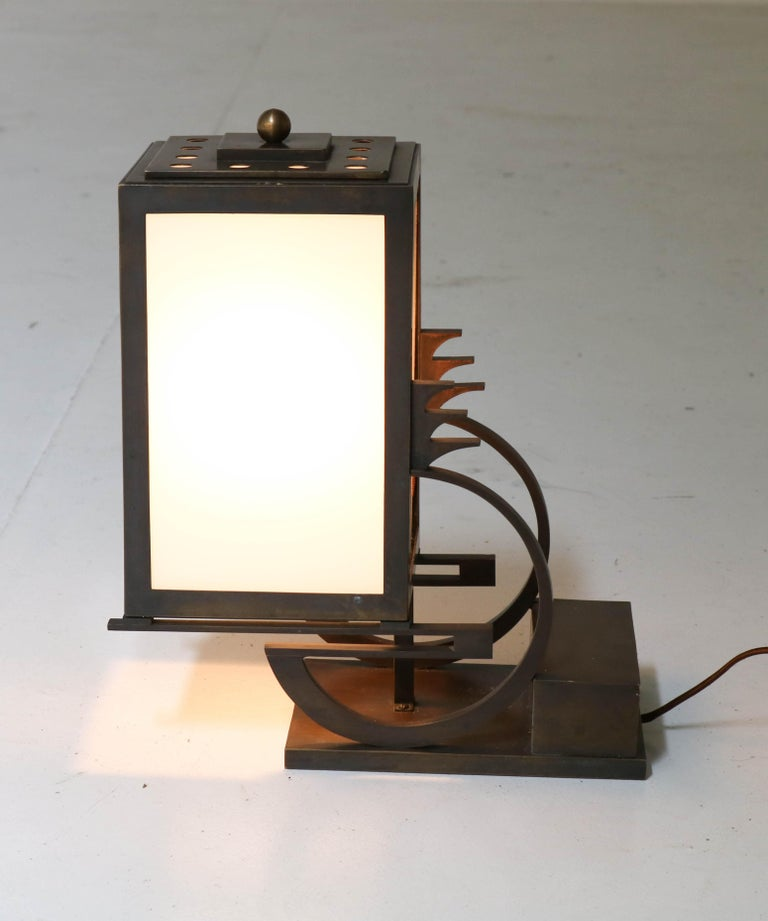 Magnificent and very rare Art Deco Haagse School table lamp. Attributed to C.J. (Karl) Gellings, a famous designer of bronze Art Deco clocks. Striking Dutch design from the 1920s. Bronze with original milk glass. Rewired for daily use. In very