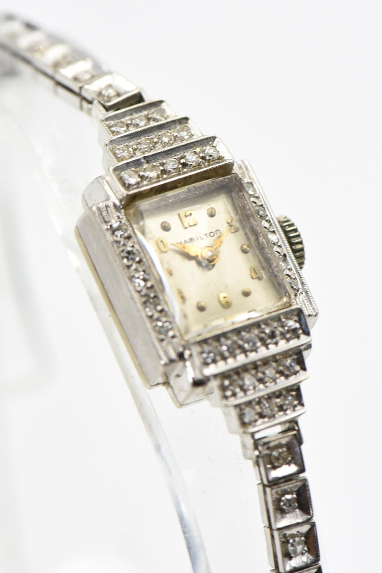 Elegant Hamilton ladies evening wrist watch featuring a rectangular face within a diamond frame.  The top and bottom have a graduated deco step design.  The band has square links with prong set diamonds inside each link.  The band terminates with a