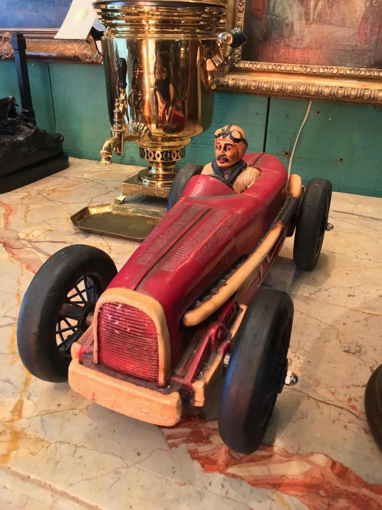 Here is a rare piece racing car with sophisticated craftsmanship and Classic form sleek body. Hand carved wood toy car. This miniature racer car model with pilot 1895-1920 the time of the beginning of the Grand Prix it would be a wonderful addition