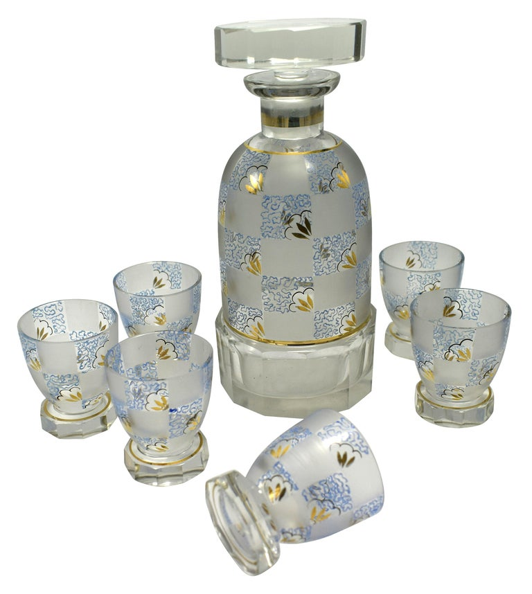 Very high quality 1930s Art Deco Czech glass decanter set. Features a Classic shape decanter with stopped and six shot sized glasses. The whole set is hand painted in beautiful soft tones of blue, black and gold enamel on a chequered background of