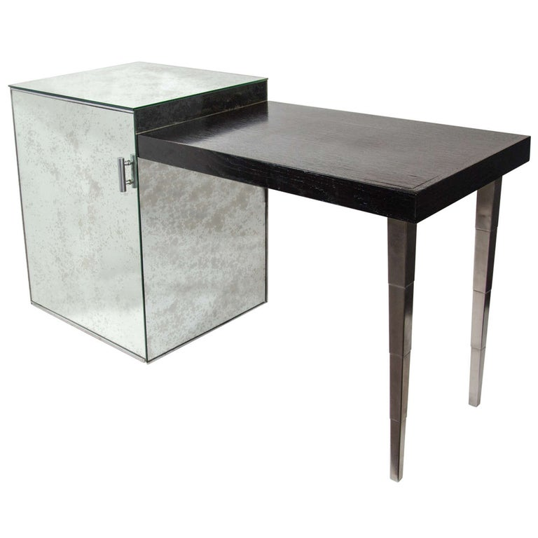 Elegant Art Deco writing table and vanity comprised of an ebonized walnut wood tabletop with an antique mirrored cabinet. The cabinet features smoked and spotted glass mirrors and has silver leaf painted interior. Features brushed nickeled support