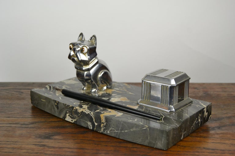 Stylish 1920s Desk Ornament,  an Inkwell with a Chromed Cubist French Bulldog Figurine.   The dog has bulging Brown Glass Eyes and is mounted on a black, grey and brown veined Marble Base , with also a chromed inkpot.  Bulldog is Signed : H. Moreau