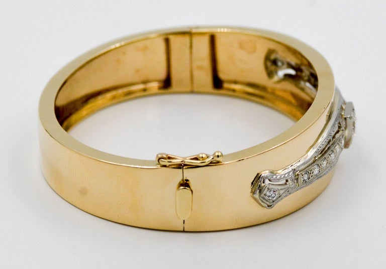 This handmade Art Deco inspired bangle is a glamorous beauty. Made in 14K white and yellow gold, this bracelet has a scintillating array of 1.00ctw (G-H color VS clarity) bezel set diamonds as the center focal point. The bracelet secures with a