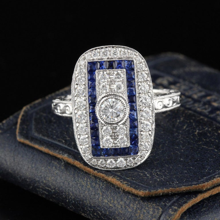 Beautiful Art Deco style ring in 18K White Gold with diamonds and channel set natural sapphires! This ring is hand engraved and mil-grained.  Item #R0047  Metal: 18K White Gold  Center Diamond Weight: 0.25 cts   Total Diamond Weight: 0.73