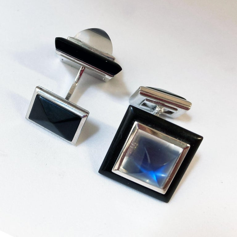 Cufflinks in 18 Kt white Gold with two pyramide - shaped Moonstones with a total weight of 11.32 ct in a bezel setting. The squarish frame is handcrafted in black Horn. This dark organic material creates the perfect contrast to the bluish shine of