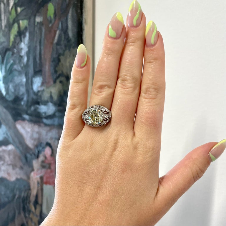 Art Deco Inspired Engagement Ring GIA 4.50 Carat Old Mine Cut Fancy Yellow Diamond Ring. The center stone is a GIA certified Old Mine Cut diamond, 4.50 carat, fancy yellow, SI2 clarity and is completely eye-clean (#6213445887). The ring itself