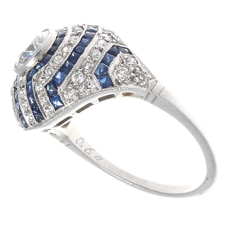 This vibrant ring pays homage to the Jazz age in the most beautiful way and designed in the Art Deco style. Featuring a sparkling old European cut diamond that is just over 0.50 carats. Surrounding the fiery facets are rows of more old European cut