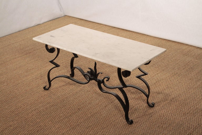 The ironwork in this coffee table from the 1950s is as uncommon as it is gorgeous. Made by a French art deco ironworker, the table features artfully and skilfully black wrought iron feet, reminiscent of Raymond Subes work, which now display stunning