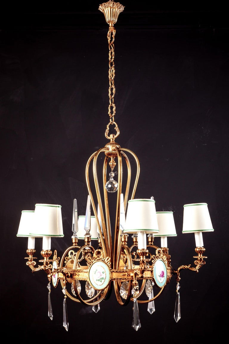 Wonderful six arm Art Deco brass chandelier with fine quality cut crystal pendants adorned with six amazing porcelain plaques decorated with colorful flowers. Newly rewired six E 14 light bulbs with a white and green rimmed shades.