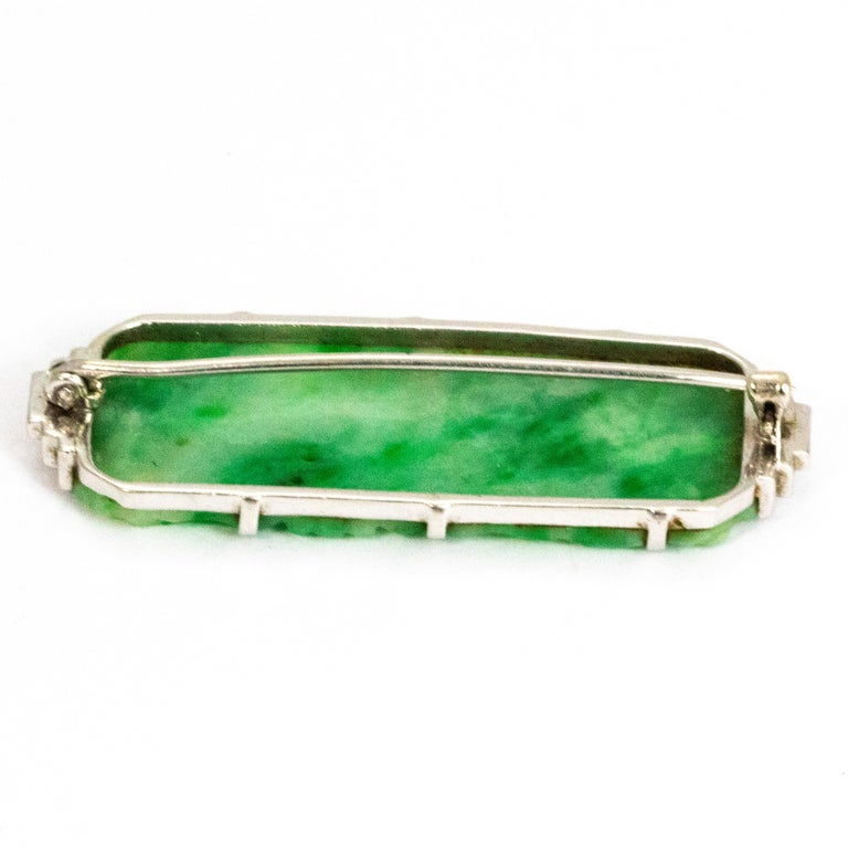 The engraving in this piece of jade is exquisite. The brooch has a classic Art Deco style to it which is shown with the white gold step detail either side of the stone. The glow when the light hits the jade is mesmerising.   Brooch Domensions: 46mm