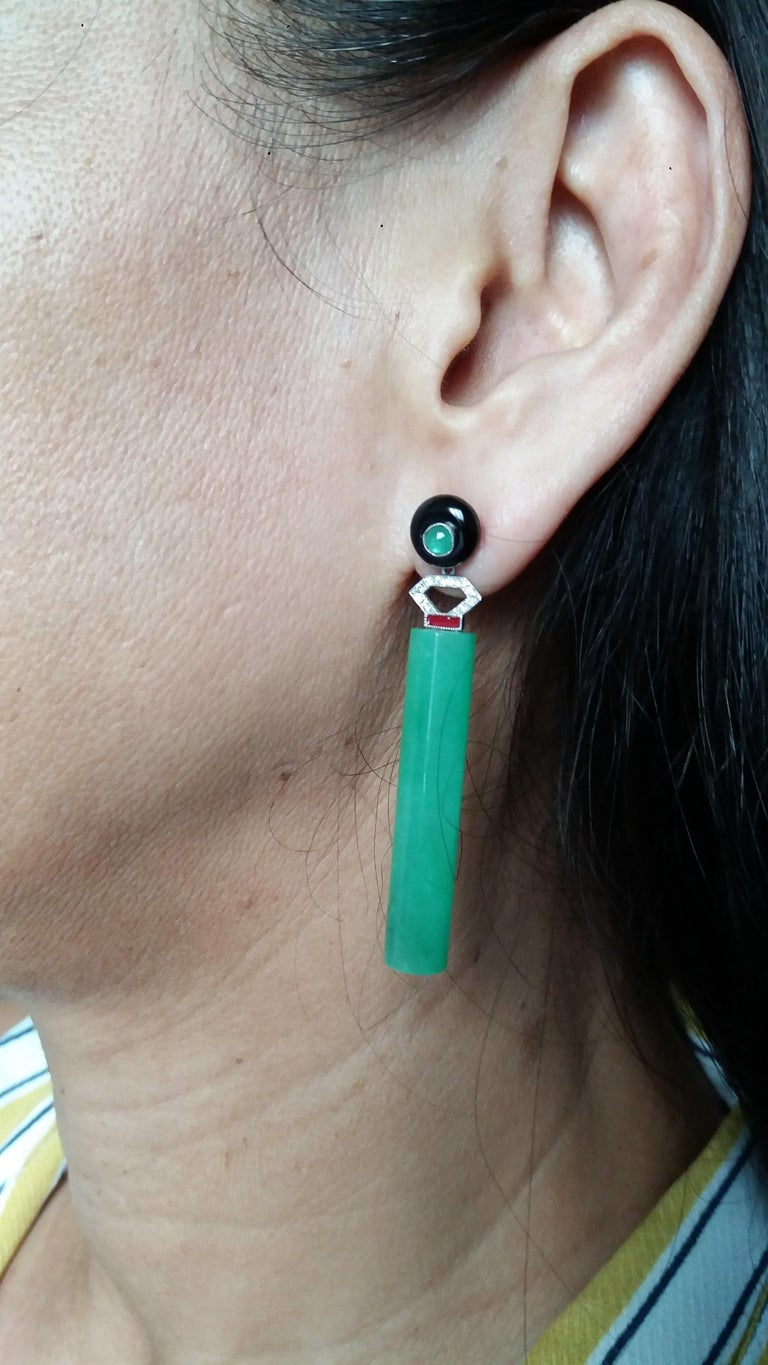 Tops are 2 round black onix buttons with small emeralds cabs in the center,middle parts in white gold,20 round full cut diamonds,red enamels,2 plain cyliders shape Burma  Jades Length 60 mm Width 8 mm Weight 14 grams In 1978 our workshop started in