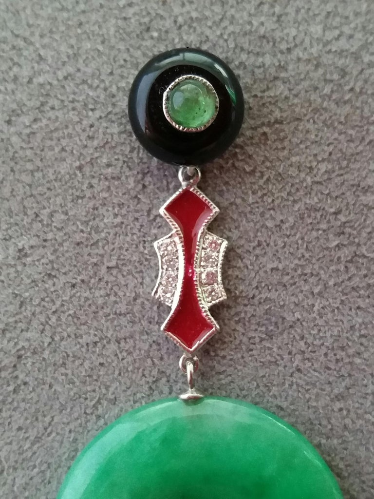 Tops are 2 round black onix of 10 mm in diameter with small emerald round cabochons in the center,middle part in white gold,small full cut diamonds and red enamel,the bottom parts are 2 Jade donuts Length 47 mm Width 21 mm Weight 8 grams In 1978 our