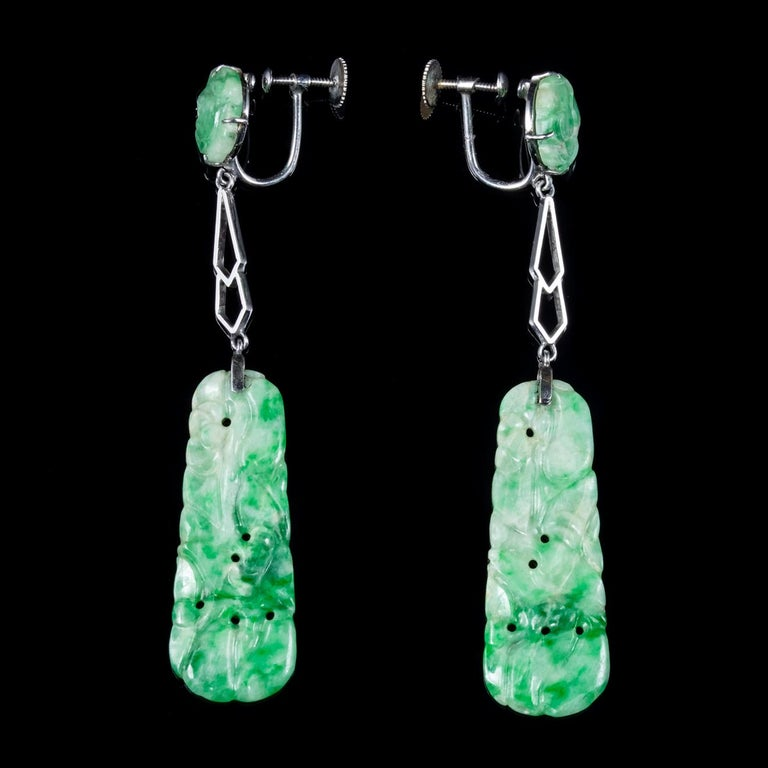 A spectacular pair of Art Deco drop earrings featuring beautiful carved Jade stones the largest of which dangles from a long gallery and displays beautiful engraved patterning.   Jade is considered the ultimate 'Dream Stone' and has been admired in