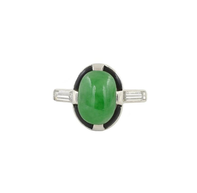 Art Deco Platinum ring with a beautiful green jade cabochon and black enamel around.  Set with 2 baguette diamonds, 0.20cts.  Circa 1930  Size 5 and easily adjustable.