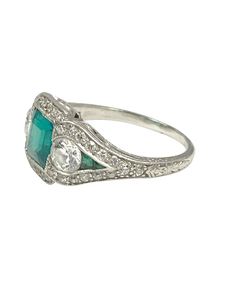 Circa 1920s J.E. Caldwell Retailed Oscar Heyman Art Deco Platinum Ring, Centrally set with a Step cut Square Emerald of approximately 1 Carat, most likely Colombian in origin and having intense fine Green color. Further set with a .33 Carat European