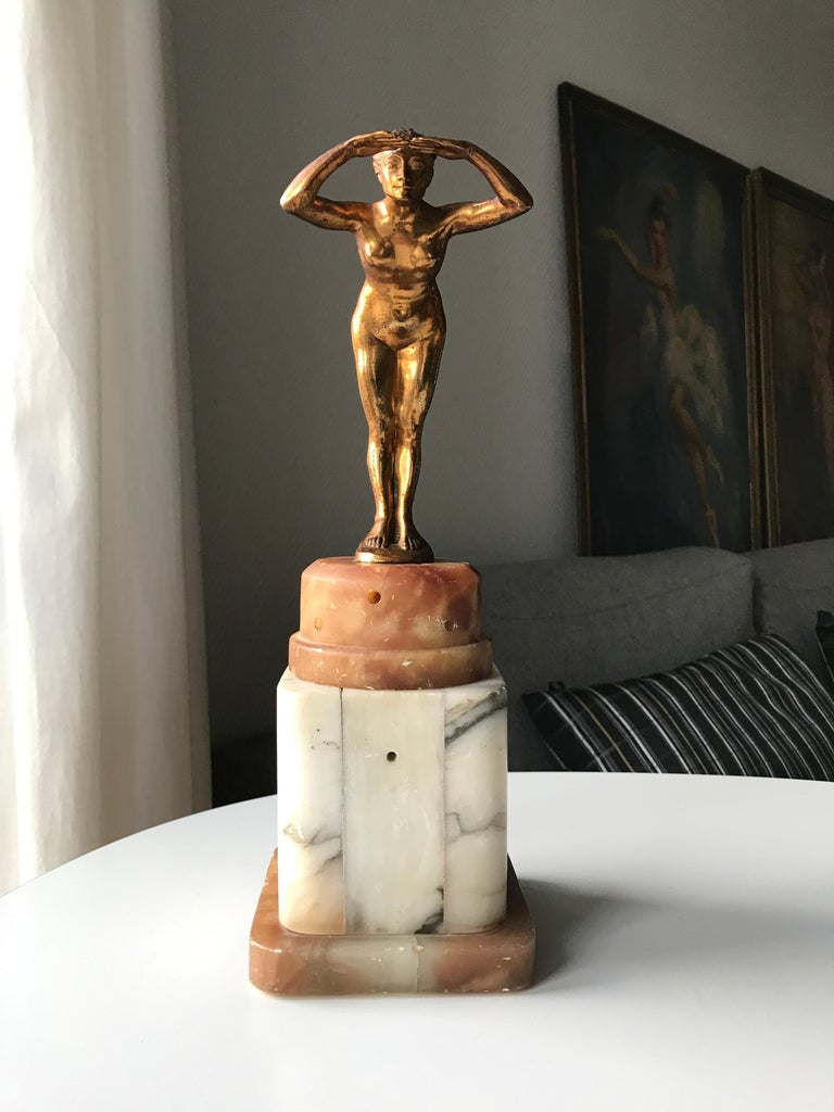 Art Deco table lamp with figurine of Naked Lady. Lamp base in two colored alabaster with marble effects. Figurine of beautiful woman made of guilted metal scouting into the horizon. The base has a function as an ozon lamp. This meant that using a