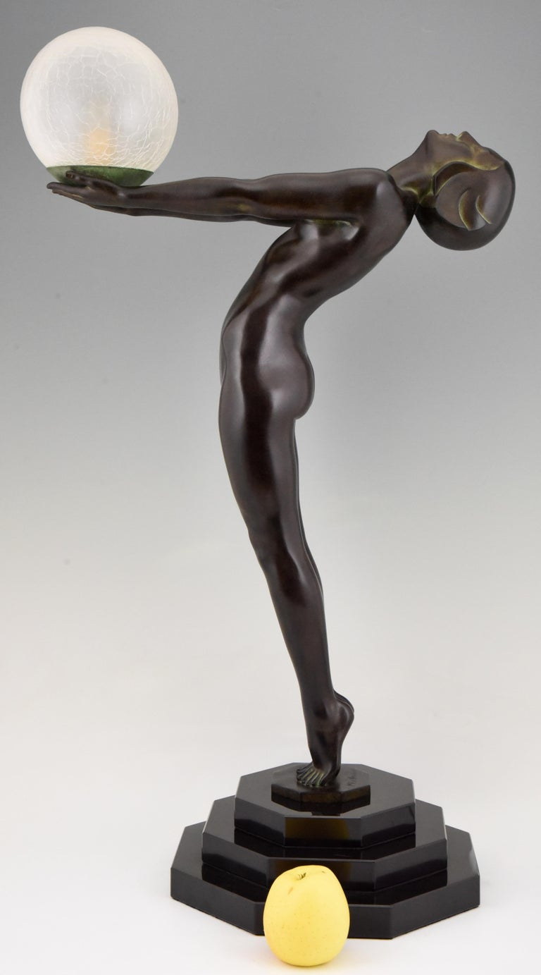 Clarte, iconic 84 cm / 33 inch tall Art Deco style figural table lamp of a standing nude holding a glass shade by Max Le Verrier with foundry mark. Designed in 1928. Posthumous contemporary cast at the Max Le Verrier foundry in Paris. Smaller