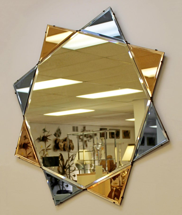 For your consideration is a captivating, large, diamond or star shaped wall mirror, with blue and pink tinted sections, despite the pink sections appearing orange in the photos; circa 1930s-1940s. In excellent antique condition. The dimensions are