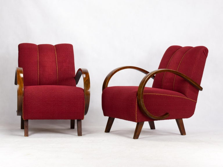 This lounge chairs, model C, were designed by Jindrich Halabala and produced in former Czechoslovakia in the 1930s by UP Zavody Brno. The chairs features curved armrests and legs made from stained beech and are upholstered in original fabric. The
