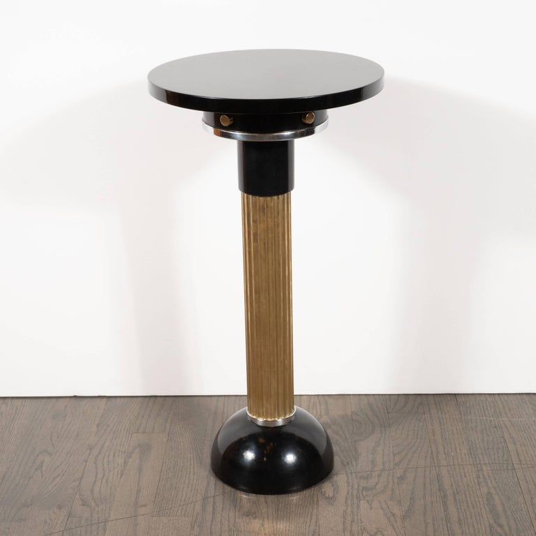 This dramatic and alluring Art Deco Machine Age drinks table was realized in the United States, circa 1935. It features a black enamel domed base; a reeded brass columnar cylindrical body and a skyscraper style top. The brass body is capped with a