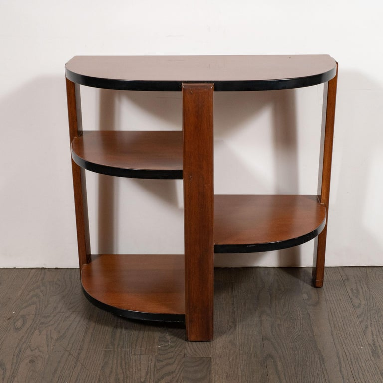 This elegant Art Deco Machine Age cubist end/side table was realized in the United States, circa 1935. It features a demilune top and three streamlined planes that connect to a central support at a perpendicular angle- all in handrubbed walnut. The