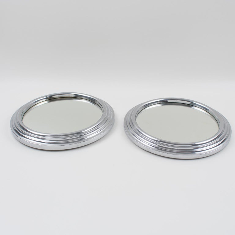 Modernist French cocktail serving tray. We have two similar pieces that can be sold as a set or individually. Machine Age industrial design with chromed metal round stepped shape and mirror insert. Measurements: 7.88 in. diameter (20 cm) x 1 in.
